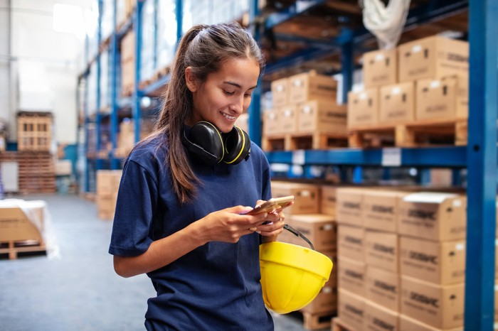 Warehouse worker checking investment account on mobile phone.