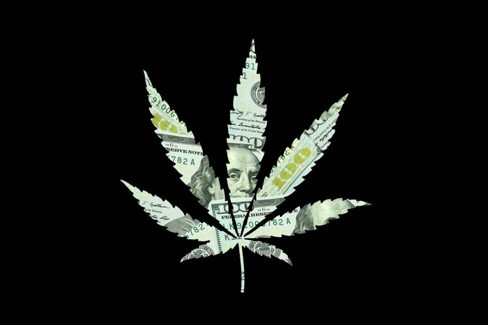 $100 bills are cut into the shape of a cannabis leaf.