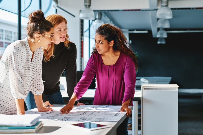 Three people looking over blueprints together at a table