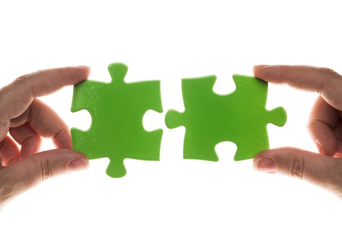 Hands holding two green jigsaw puzzle pieces close to each other.