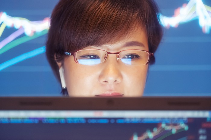 Person wearing glasses in front of a PC screen with a large stock chart displayed in the background.