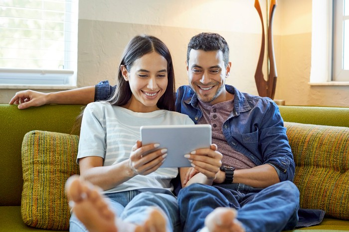 Two smiling people on a couch looking at a touchscreen tablet