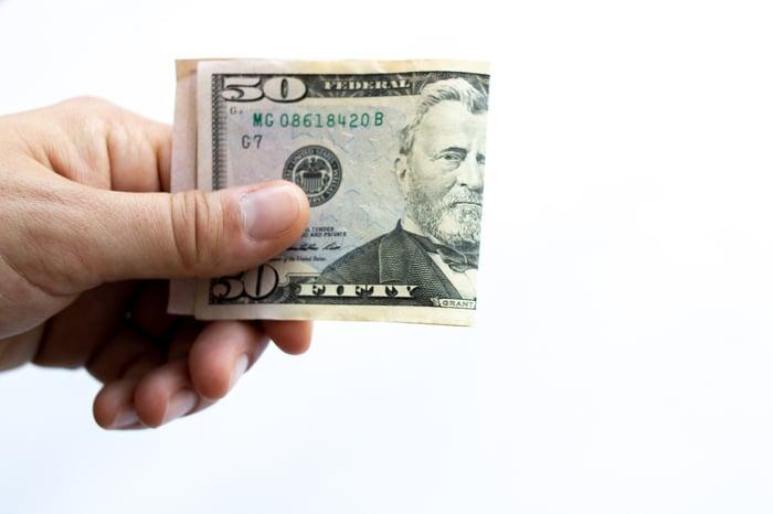 Hand holding $50 bill folded in half