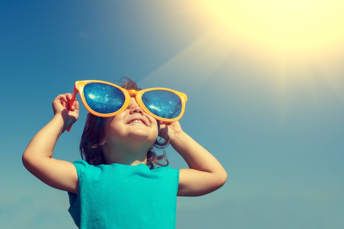 Young girl child looks through giant sunglasses at sky.