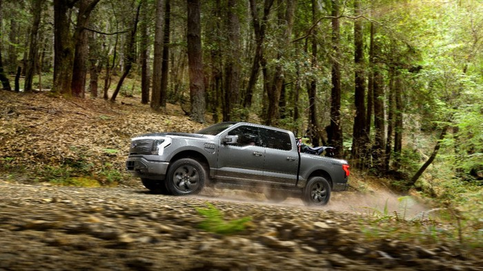 A Ford F-150 Lightning driving in a forest.