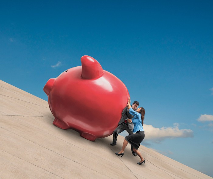 Two people pushing a large piggy bank up an incline.