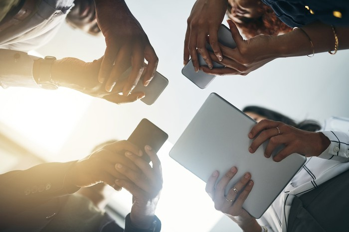 Four people stand in circle and look at their electronic devices seen from ground up.
