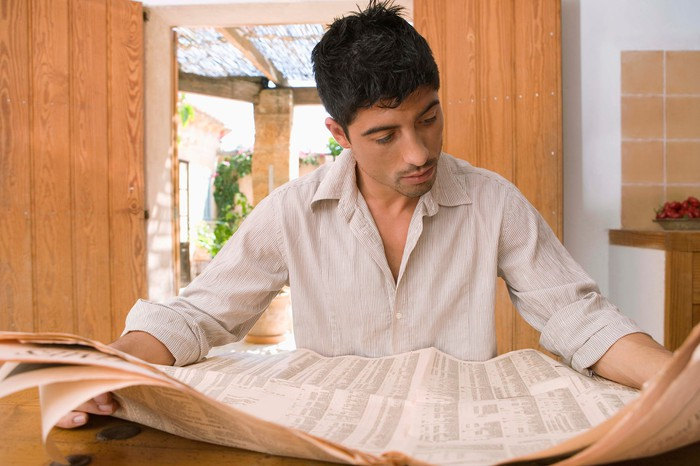 A man reading a financial newspaper in his home.