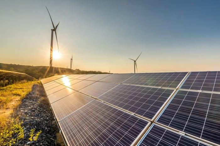 Solar panels and wind turbines at dawn.