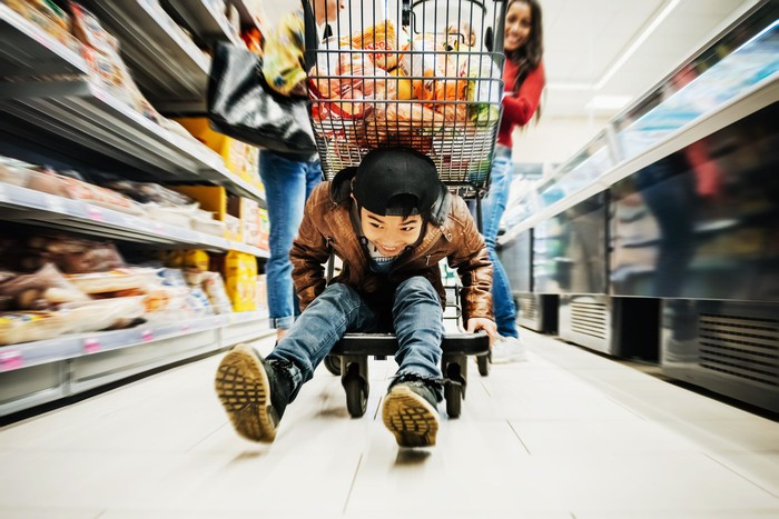 A young boy on a trolley walking down a supermarket aisle.