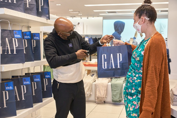A Gap employee in a store with a customer holding a Gap bag.