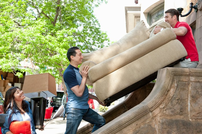 Two people moving a large sofa outside of a home.