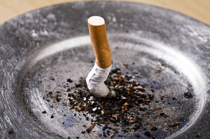 A cigarette butt smashed into an ash tray.