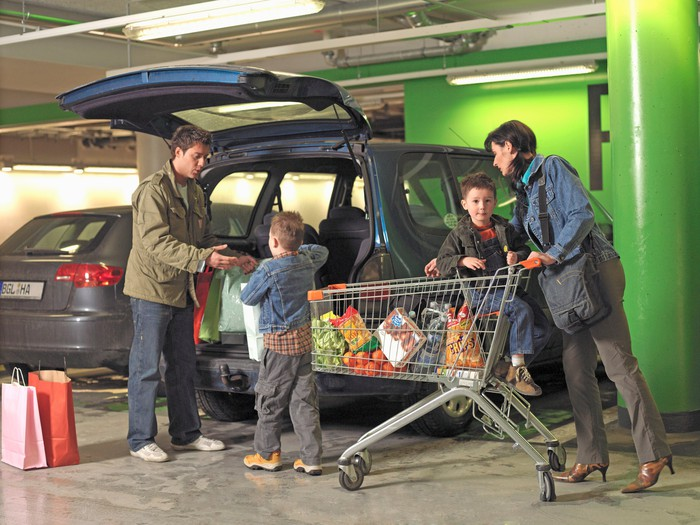 A family taking a cart full of groceries to their car.