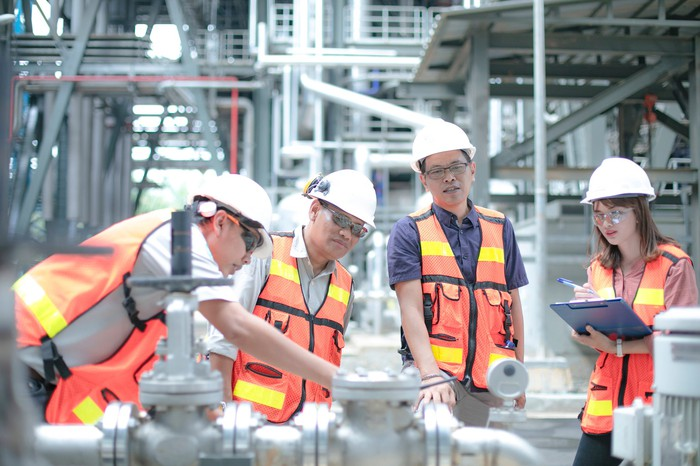 Four people in protective gear in an energy processing facility.