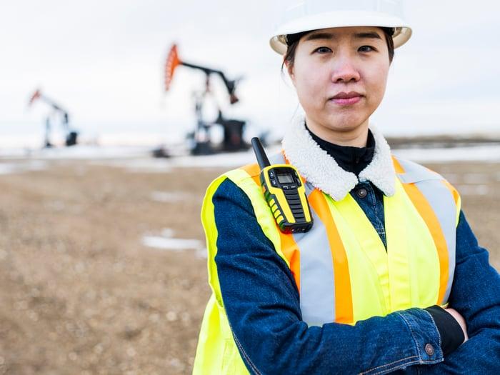 Une personne en tenue de protection avec des puits de pétrole en arrière-plan.