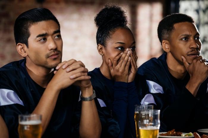 Trois personnes dans un bar ont l'air nerveuses, avec des verres de bière devant elles.