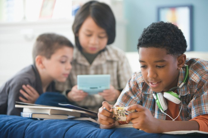 Three kids playing games on mobile devices.