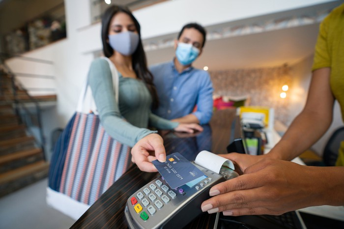 Masked shoppers use touchless card technology at checkout.
