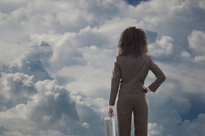 Person carrying briefcase looking at clouds.