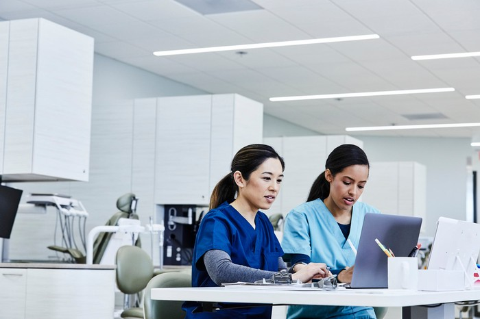 Two healthcare workers sitting at a computer and writing things down.