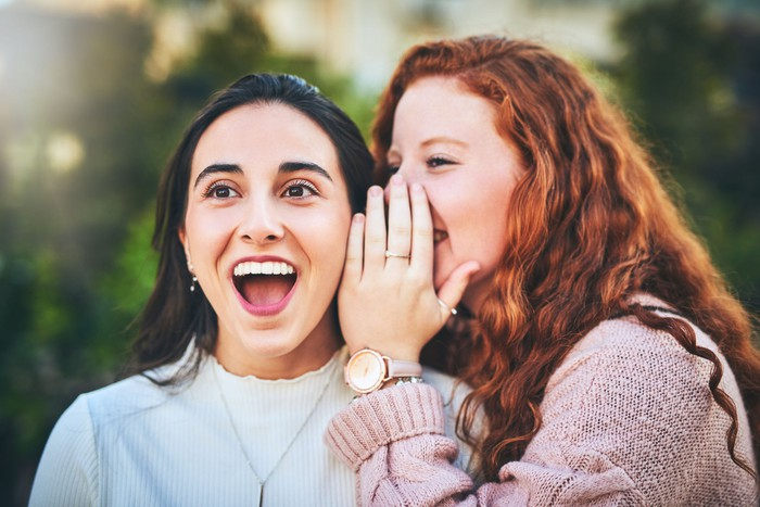 One woman whispering into the ear of another woman, who is pleasantly surprised by what she is hearing.