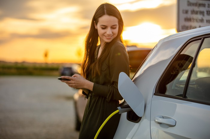 A person using an electric vehicle charger.