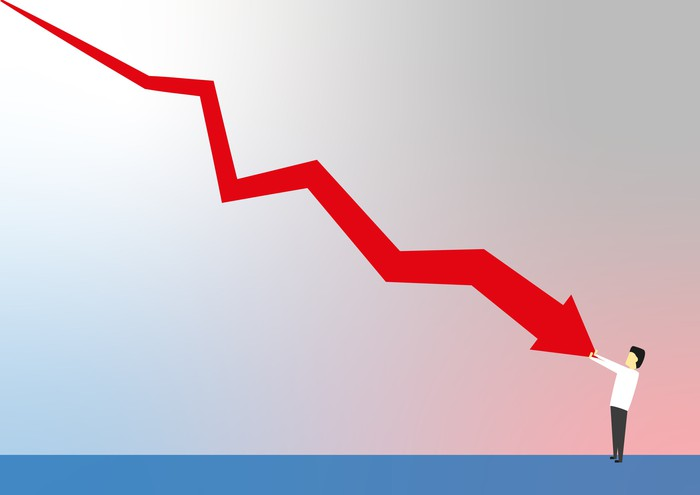 Man stopping a red arrow chart from falling any farther.