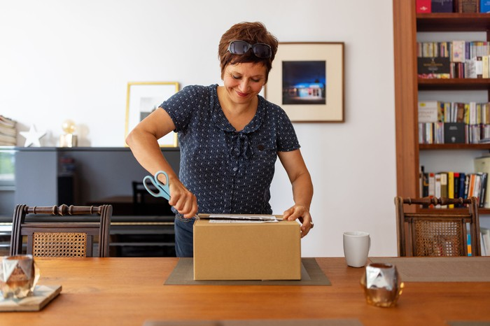 A person using scissors to open up a brown box on a table.