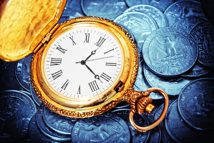 A pocket watch on a pile of coins.