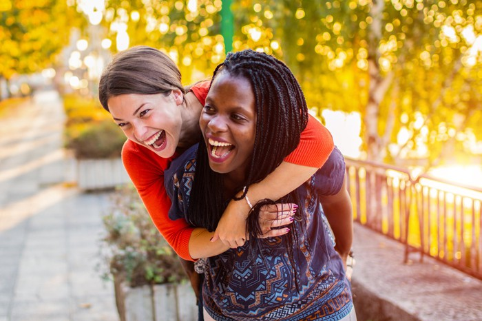 Two friends outdoors, hugging and laughing.