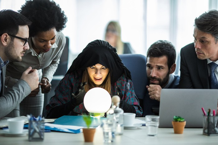 Woman looking at crystal ball at an office desk with team