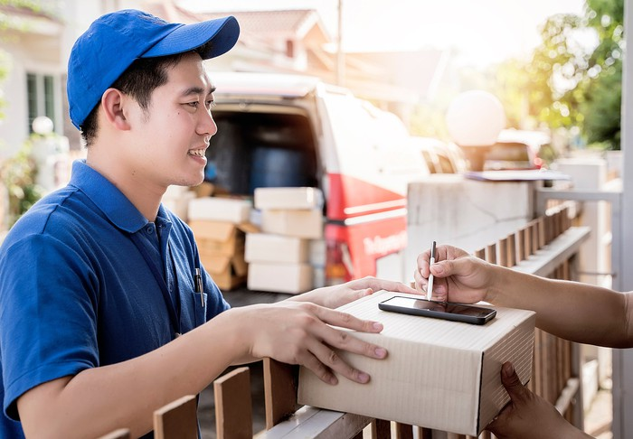 An Asian man delivers a package to someone signing on their smartphone