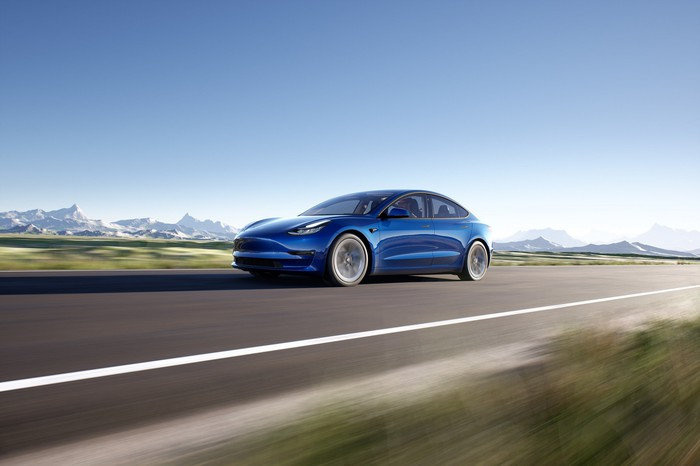 Tesla Model 3 speeding down road with snowy mountains in the background.