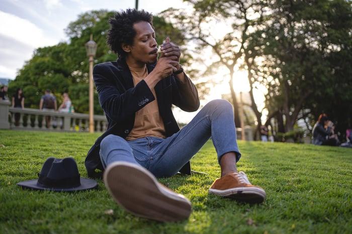 Man smoking cannabis while sitting in a park.