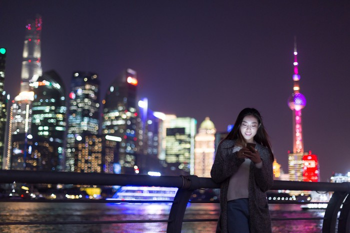 Person using mobile phone at night in a large city.