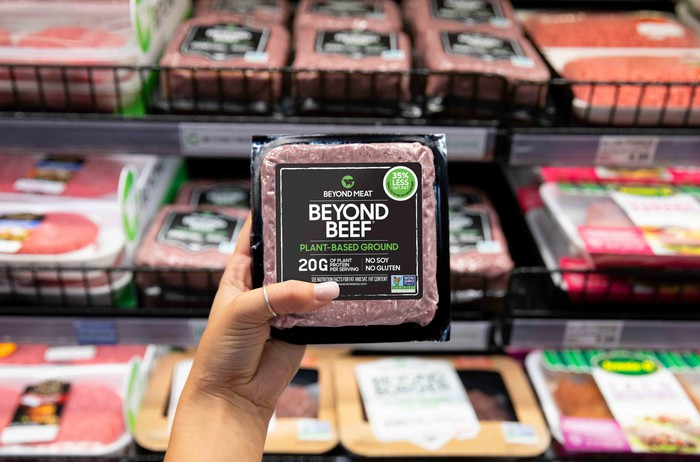Hand holding a Beyond Beef package at a grocery store