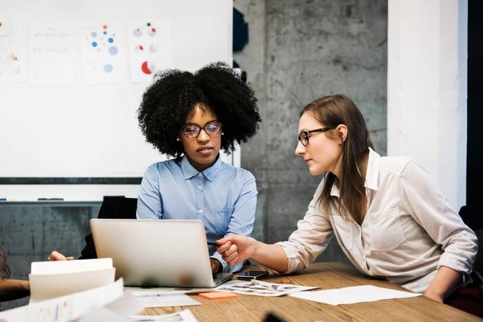 Two businesswomen work on a laptop in an office.