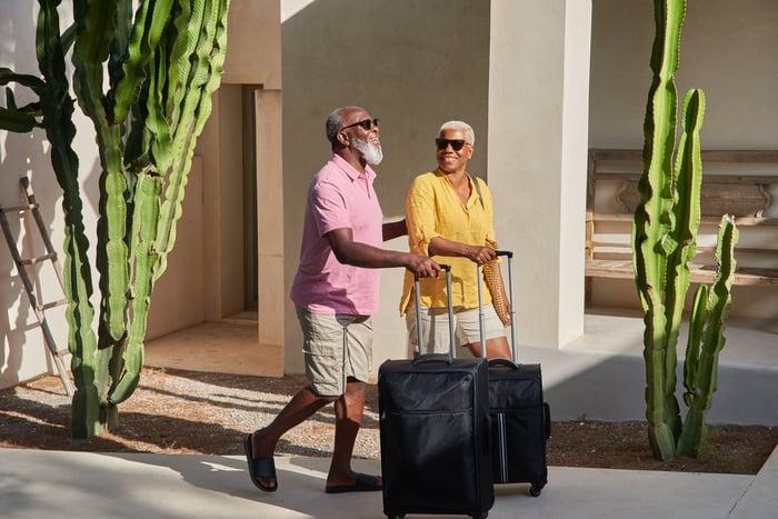 A mature couple smile while wheeling suitcases near a hose.