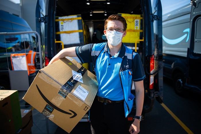 A delivery driver from Amazon wears a facemask while holding a package.