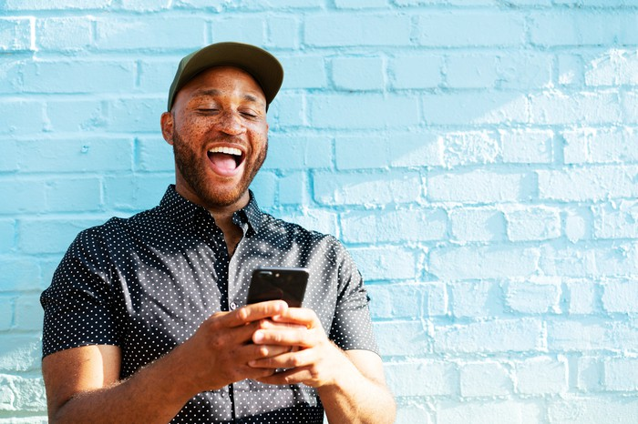 A person appears to laugh out loud while looking at a smartphone and standing in front of a blue brick wall.