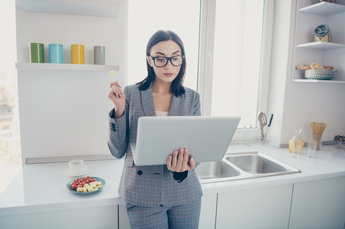 A woman in a kitchen holding a laptop and eating cheese.