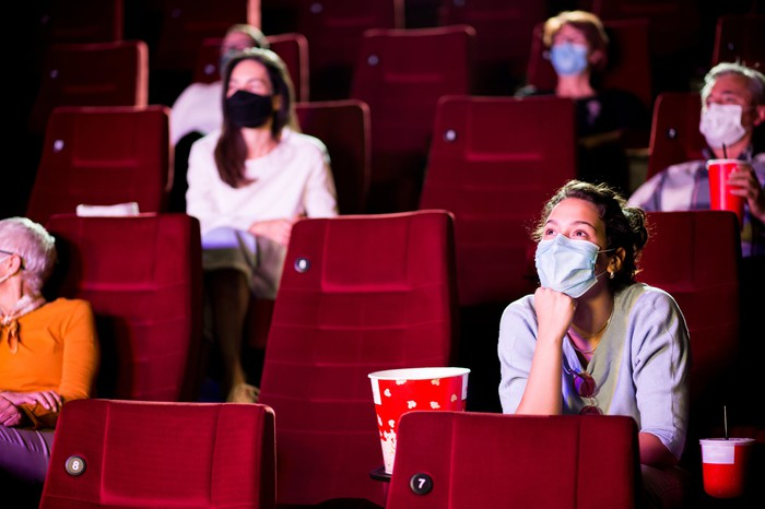 People wearing masks watching a movie in a theater