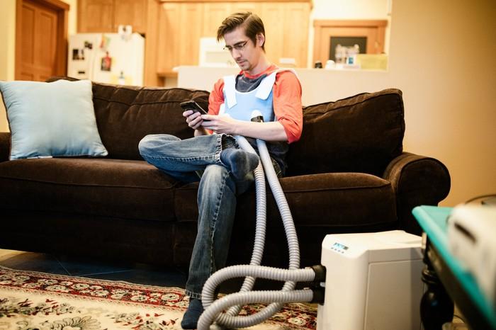 A person sitting on a sofa wearing a  high-frequency chest oscillation system for cystic fibrosis patients.