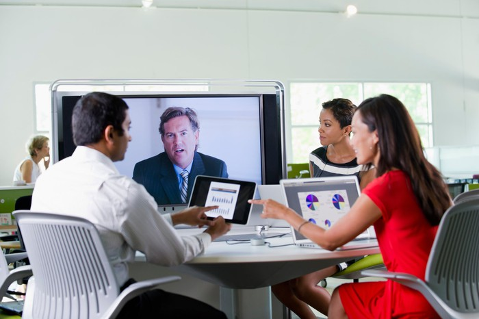 Several people around a table talking while someone is on a video screen.