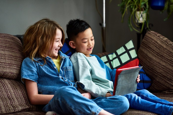 Two kids sitting on a couch, and looking at a tablet.