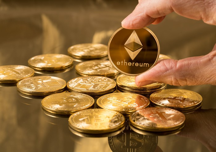 A person holding up a gold-colored Ethereum coin, with the logo printed on the coin.