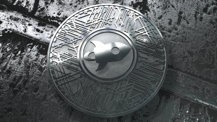 An up-close view of a silver Stellar Lumens coin with a rocket ship logo emblazoned on the coin.