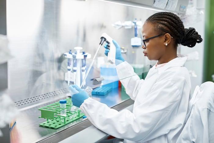 Mulher usando pipeta para tirar fluido de um frasco em um laboratório.