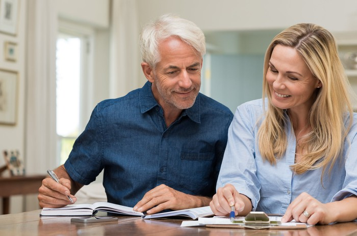 Two older people smiling while working at a desk and taking notes.